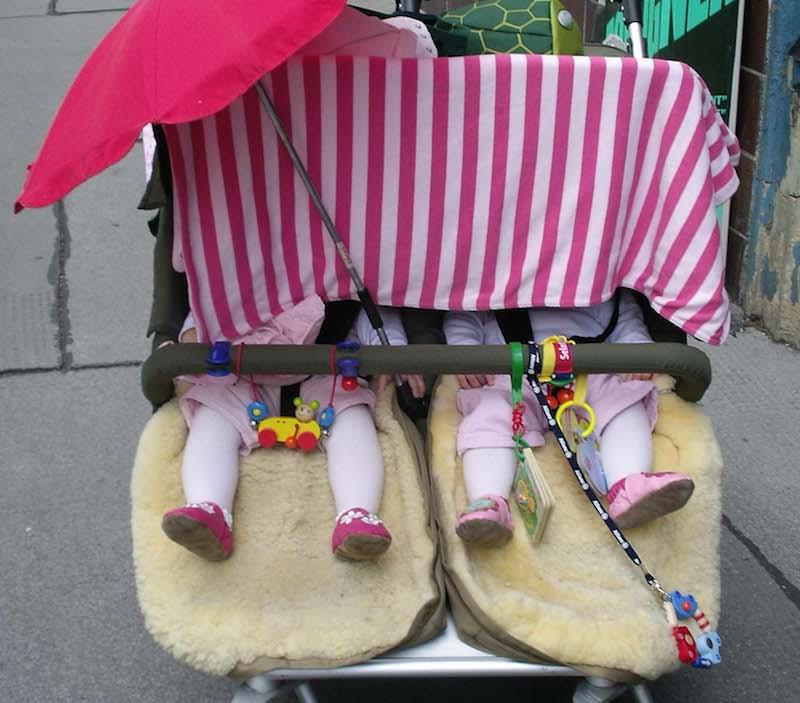 zwei Kinder im Kinderwagen