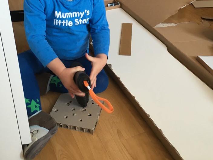 Große Hilfe beim Aufbauen. Kind mit elektrischen Schraubendreher.